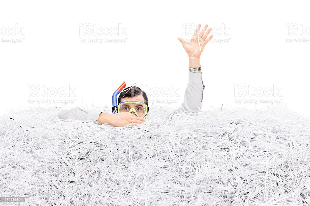 Man diving in a pile of shredded paper stock photo