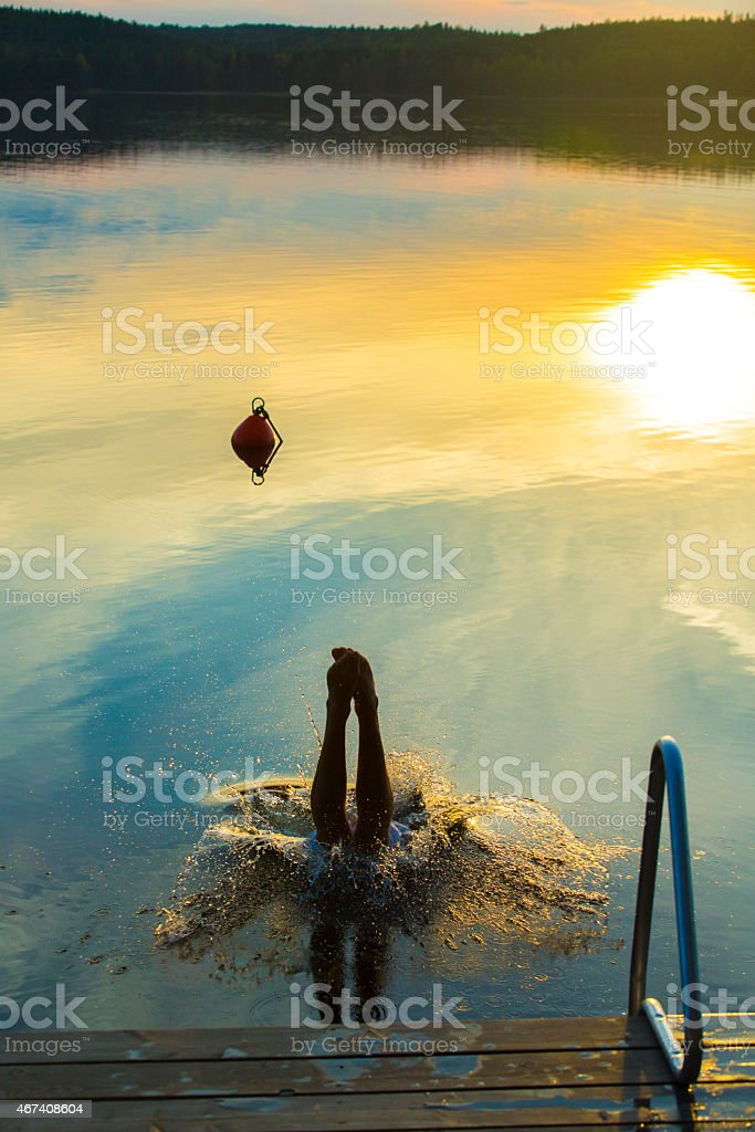 Man Diving Into A Lake Head First After Sauna stock photo