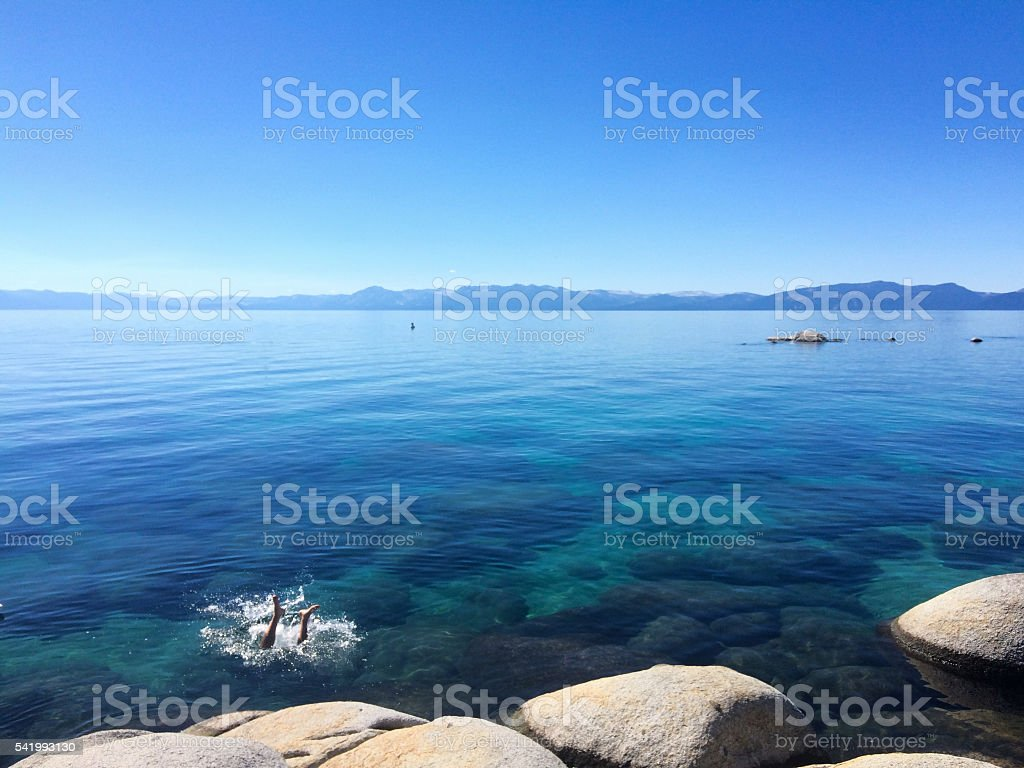 Man diving into Lake Tahoe in summer stock photo