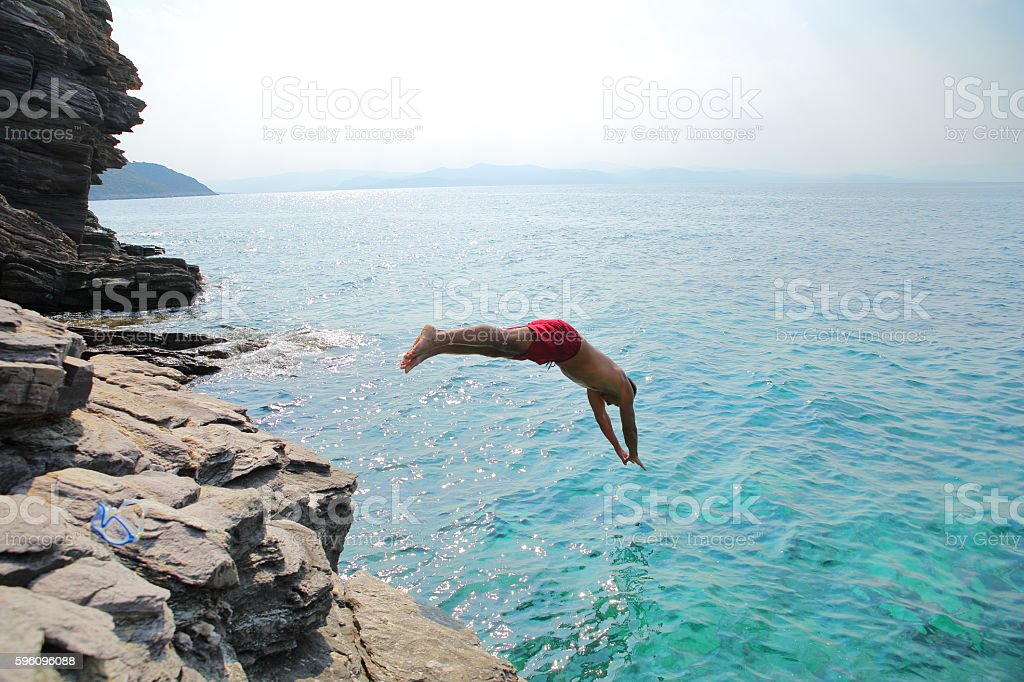 man diving into sea stock photo