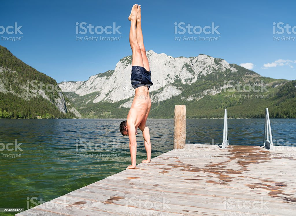 Man doing a handstand on a pier, Lake Altaussee, Austria stock photo