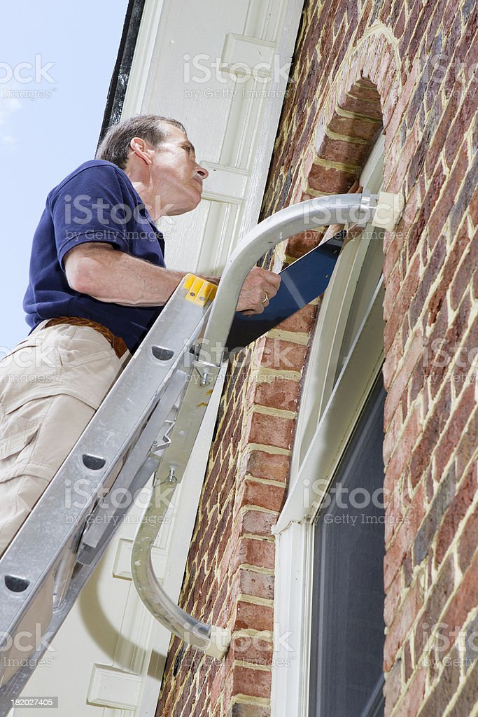 Man doing a residential window inspection royalty-free stock photo