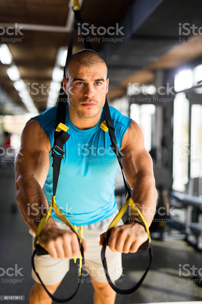 Man doing arm exercises with suspension straps at gym. stock photo