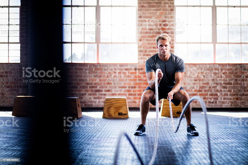 Man doing battle ropes exercise during crossfit training at gym stock photo