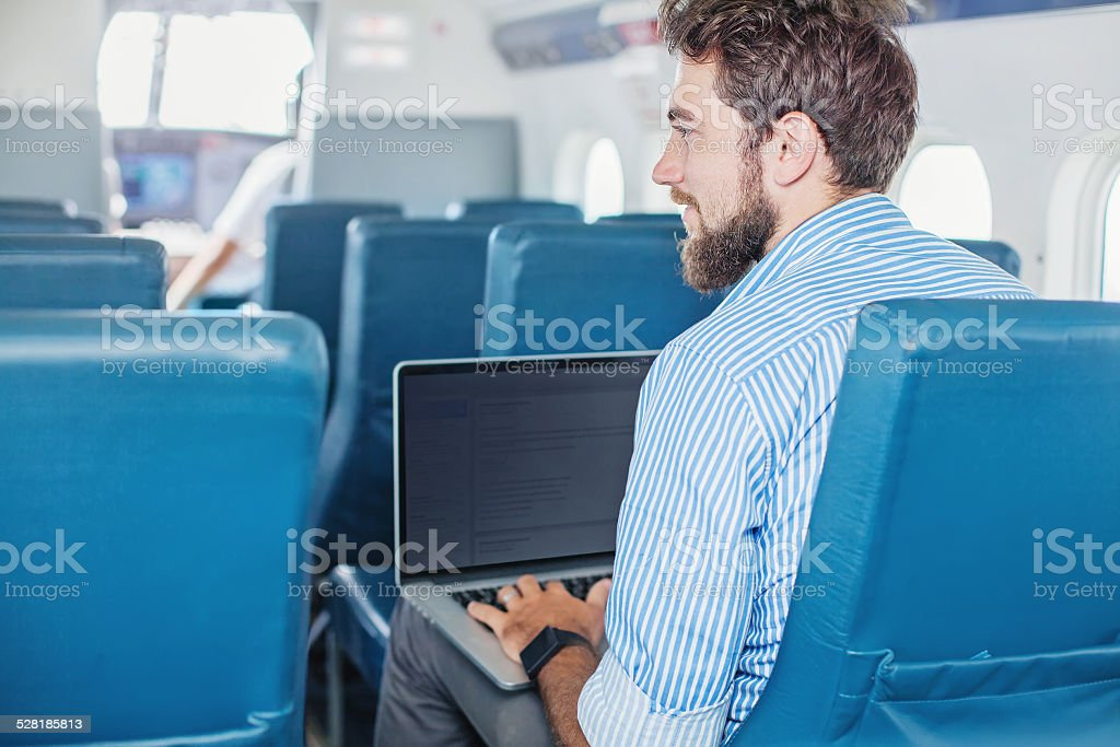 Man doing business in the airplane stock photo