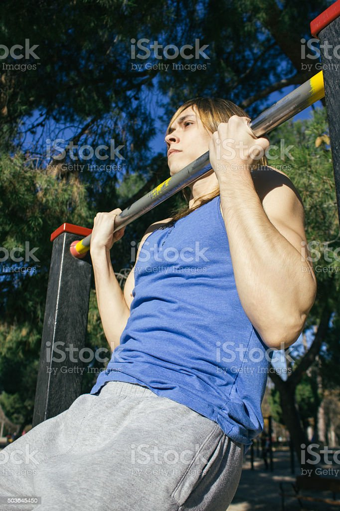 Man doing chin ups in a bar during stock photo