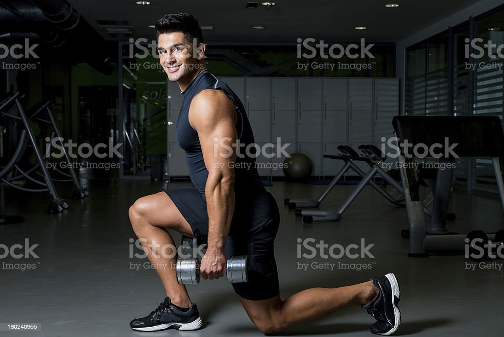 A man doing dumbbell lunges in a gym stock photo