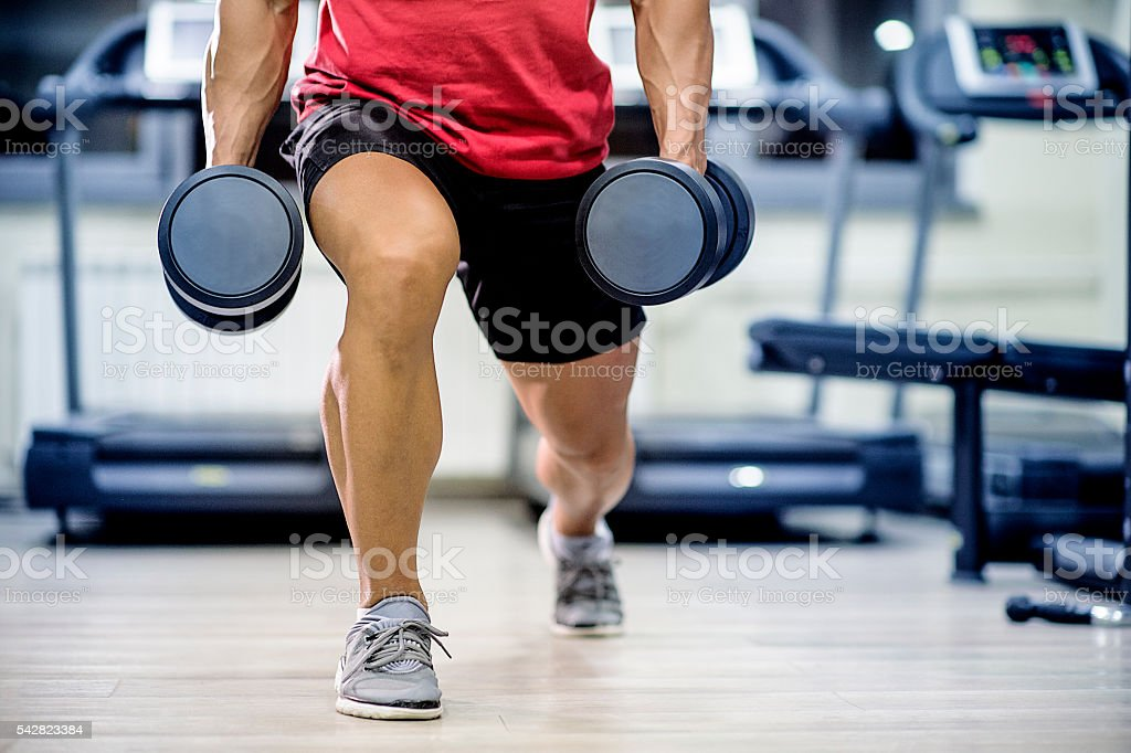 Man doing dumbbell stepping lunge stock photo