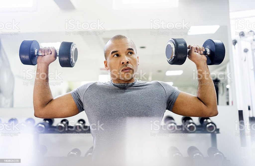 Man doing exercise with dumbbells at gym royalty-free stock photo