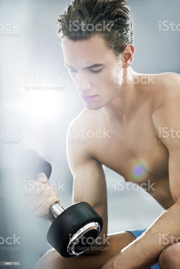 Man doing exercises with dumbbells at a gym. royalty-free stock photo