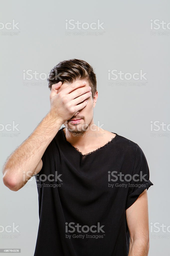 Man doing facepalm covering his eyes and face with palm stock photo