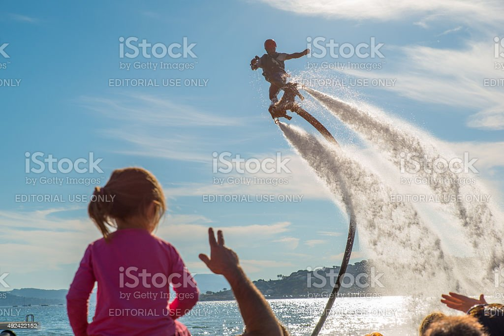 Man doing flyboards in front of child. stock photo