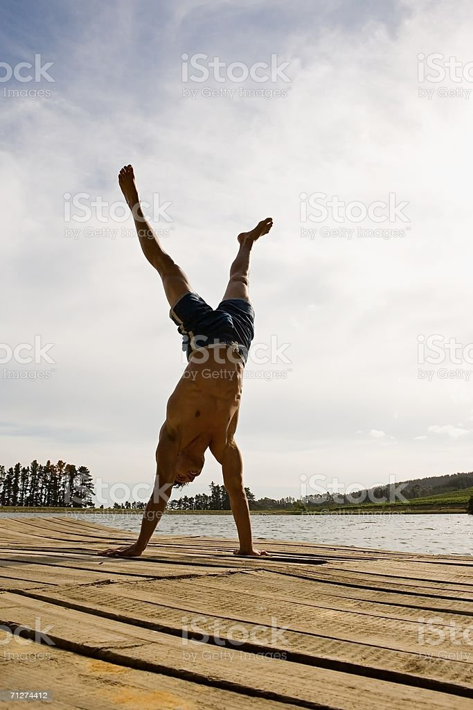 Man doing handstand on a jetty stock photo
