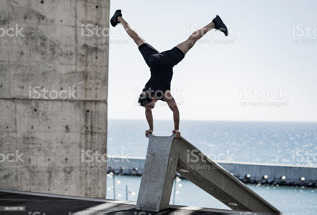 Man doing headstand in the city stock photo