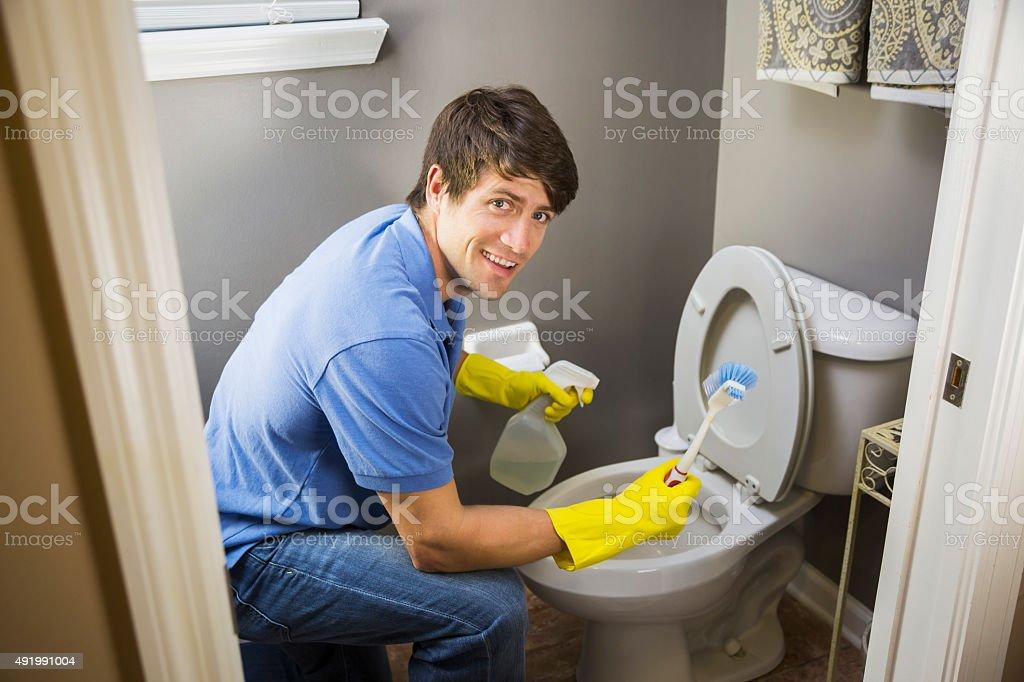 Man doing housework, cleaning bathroom toilet stock photo