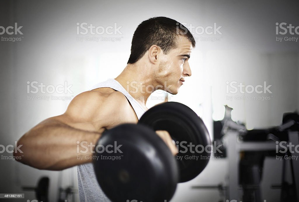 Man doing lateral lifts in a gym. stock photo