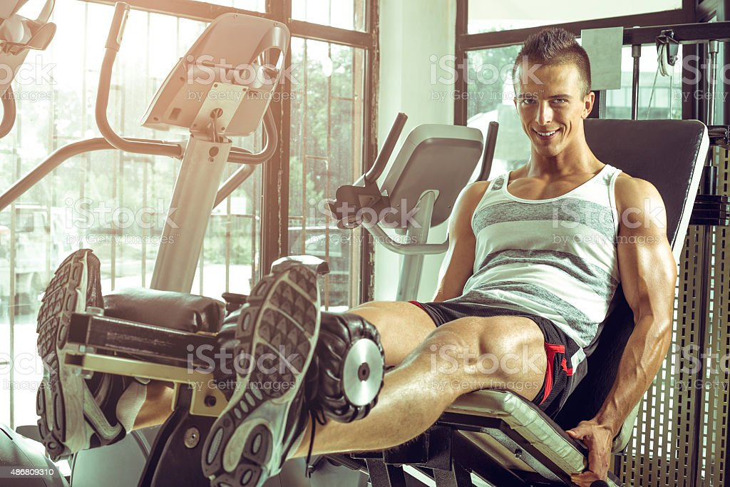Man doing leg extension in gym stock photo