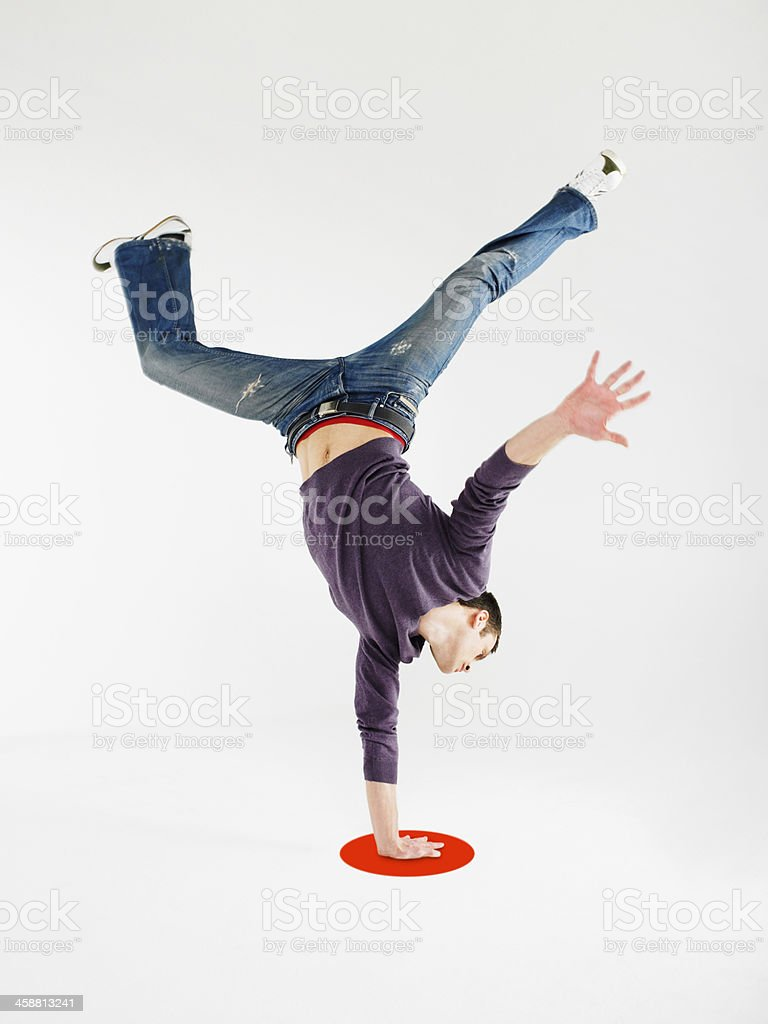 Man Doing One Handed Handstand On Red Dot stock photo