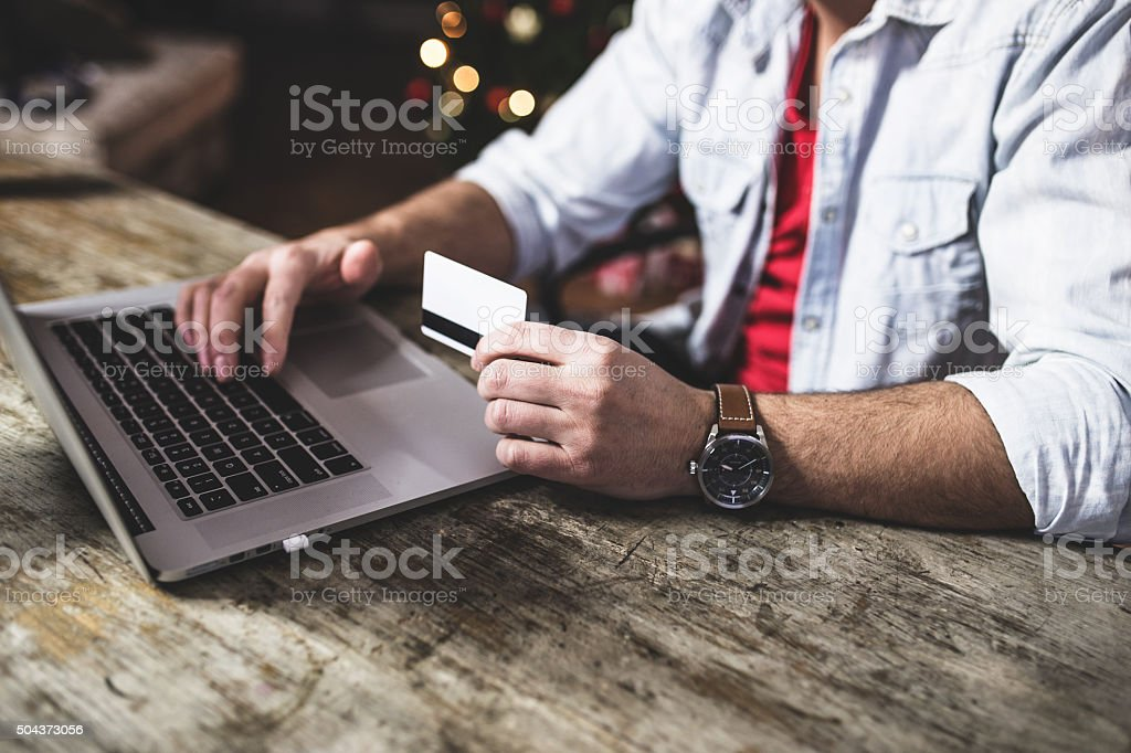 Man doing online shopping with credit card on laptop stock photo