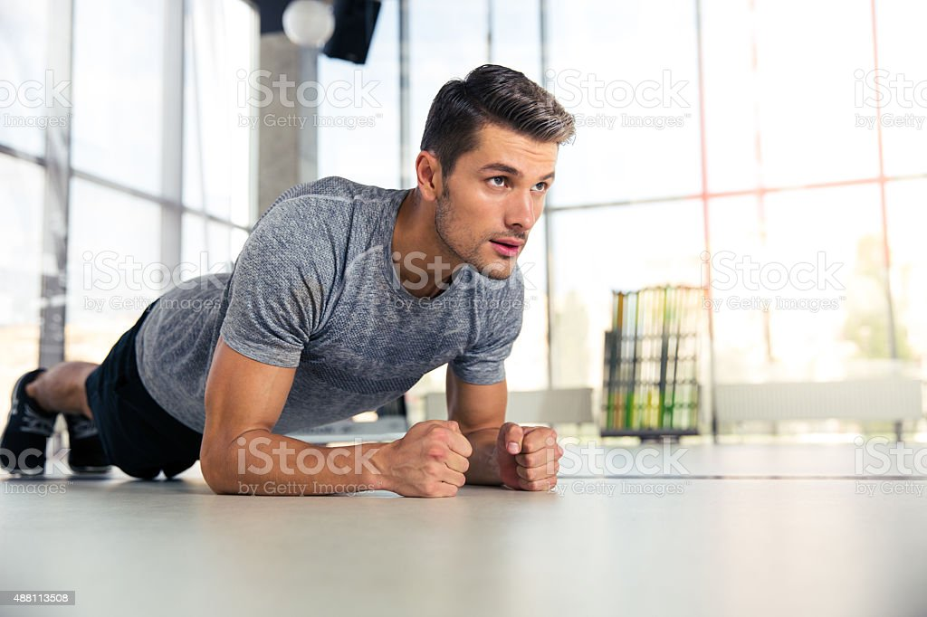 Man doing planking exercise in gym stock photo