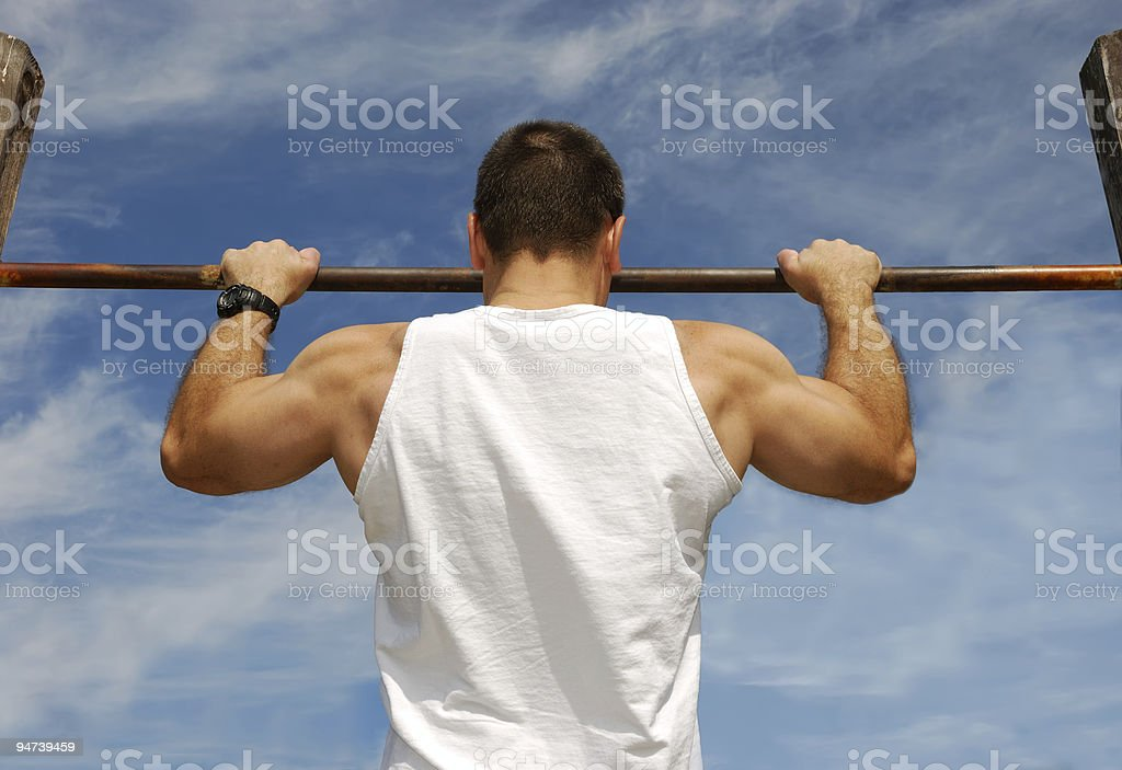 A man doing pull ups in front of a blue sky royalty-free stock photo