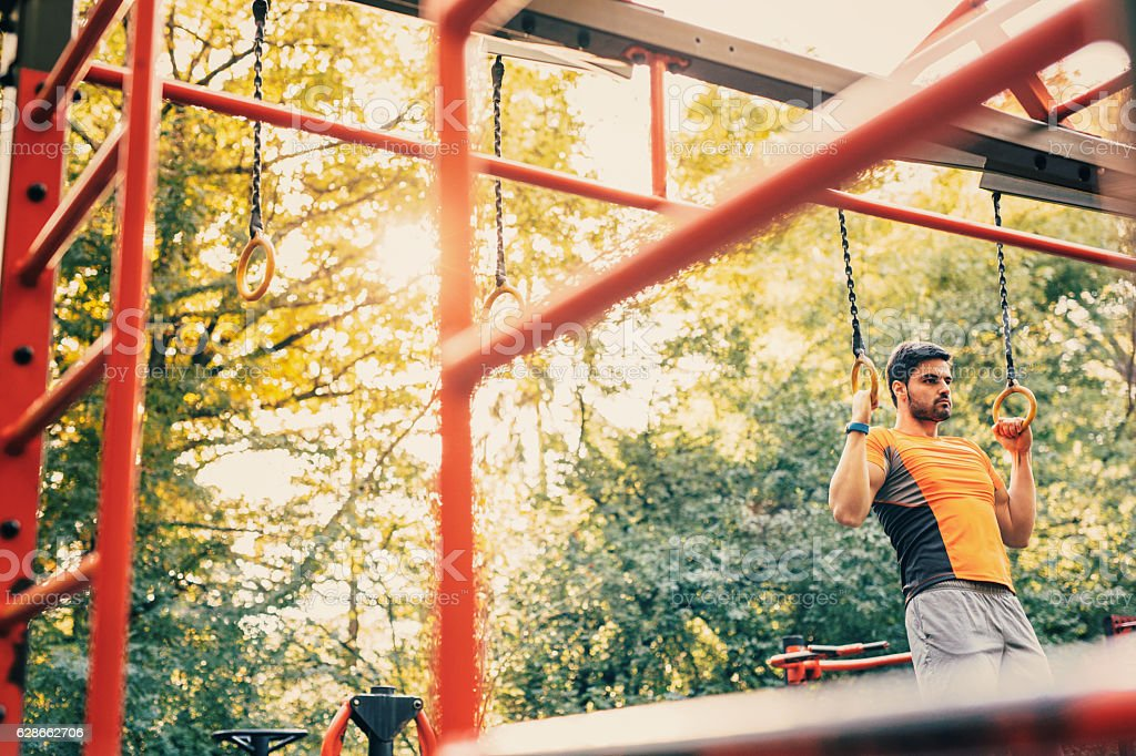 Man doing pull ups in the park stock photo