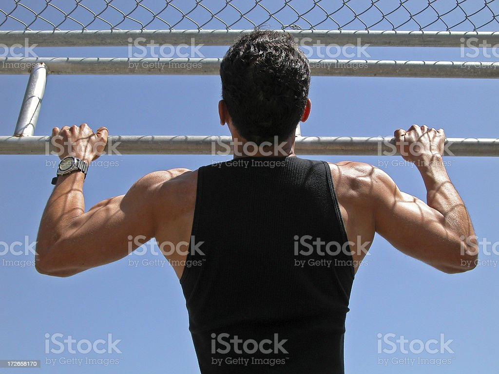Man doing pullups outdoors stock photo