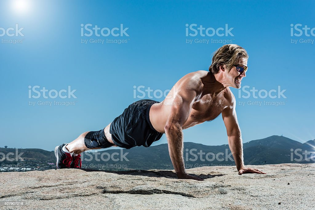 Man Doing Push Ups In The Mountains stock photo