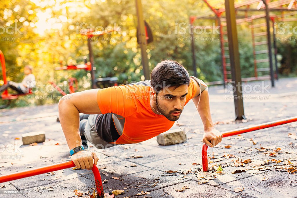 Man doing push ups in the park stock photo