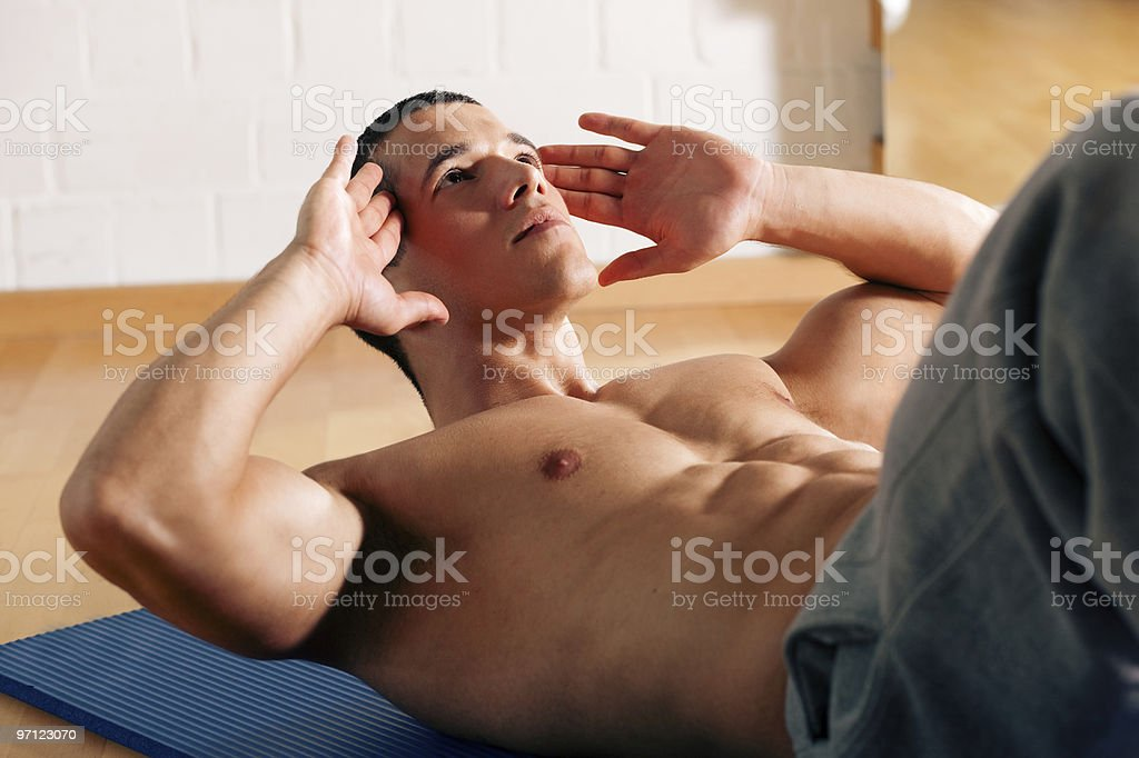 Man doing push-ups in a gym with his shirt off stock photo