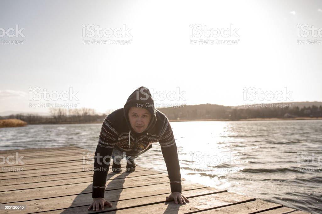 man doing push-ups on lake pier stock photo