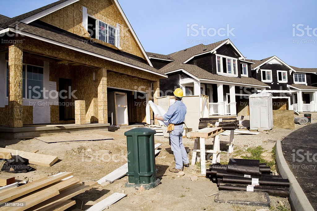 Man doing quality control inspection of a house being built stock photo