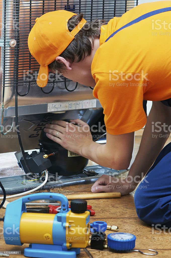 A man doing repair work on a refrigerator royalty-free stock photo