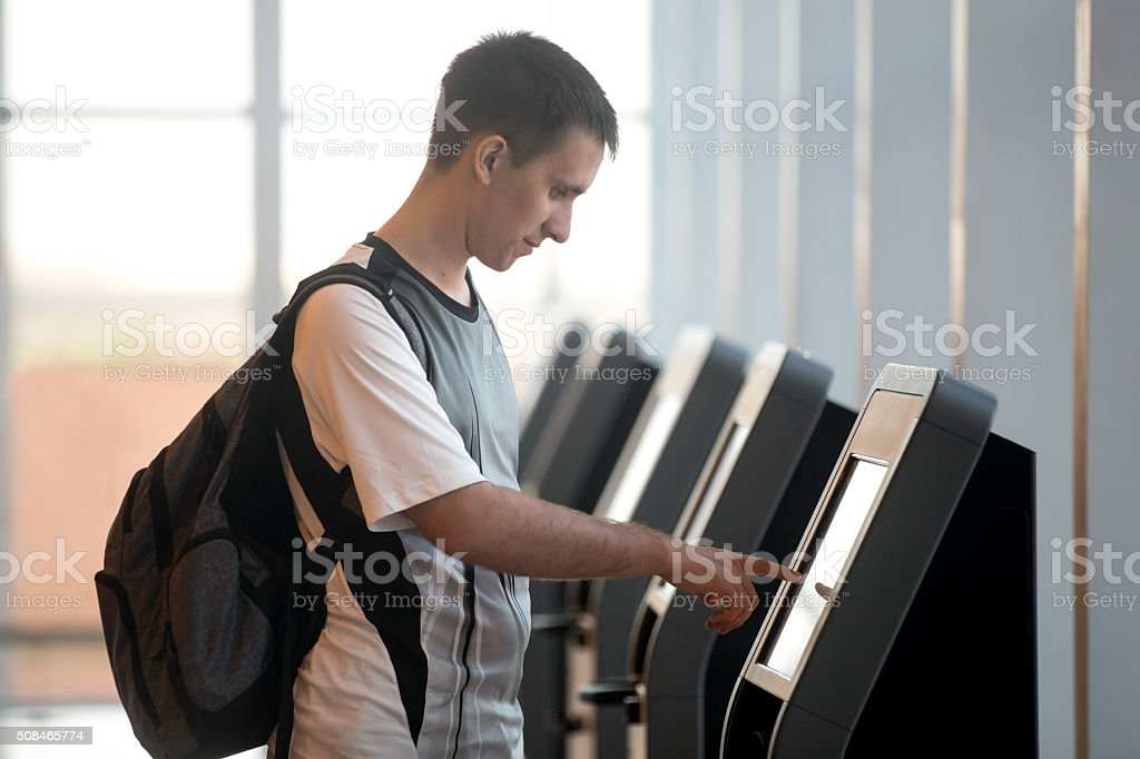Man doing self-registration for flight stock photo