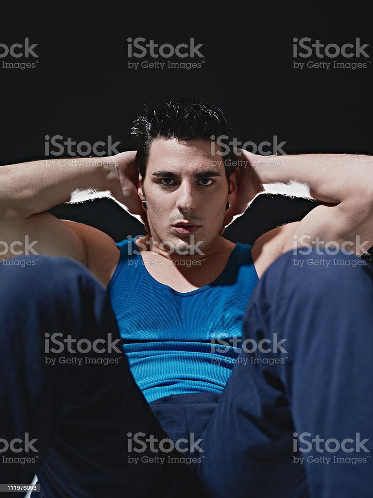 man doing series of sit-ups on black background royalty-free stock photo