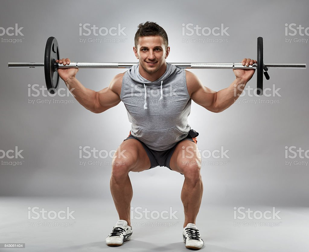 Man doing squats with barbell stock photo