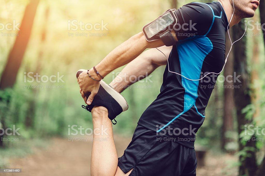 Man doing stretching exrecises in the park stock photo