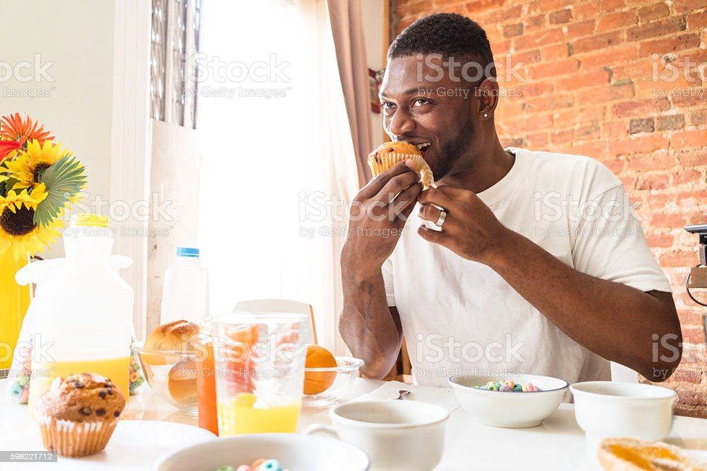 man doing the breakfast at home with muffin stock photo