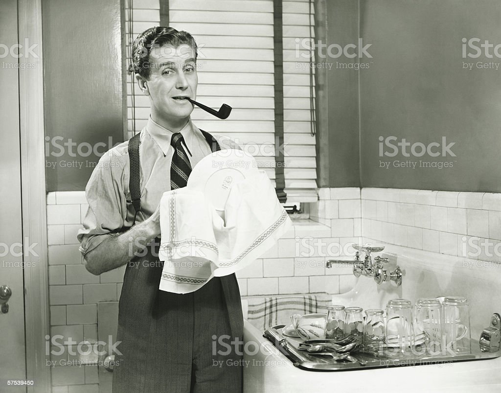 Man doing washing dishes in kitchen, pipe in teeth, (B&W) stock photo