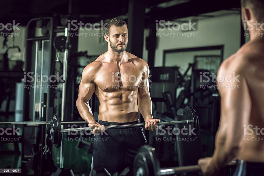 Man doing weight lifting in gym stock photo
