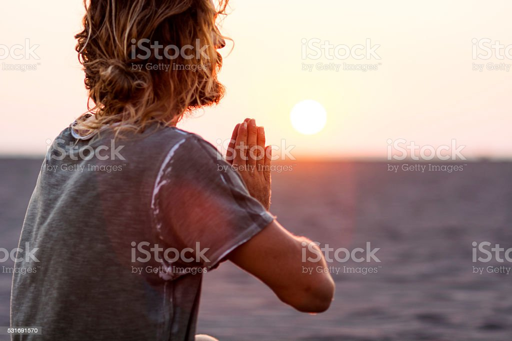 Man doing yoga at the beach stock photo