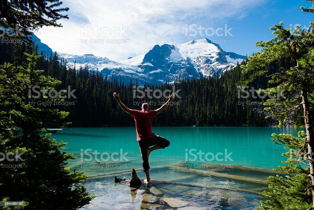 Man doing yoga in the mountains stock photo