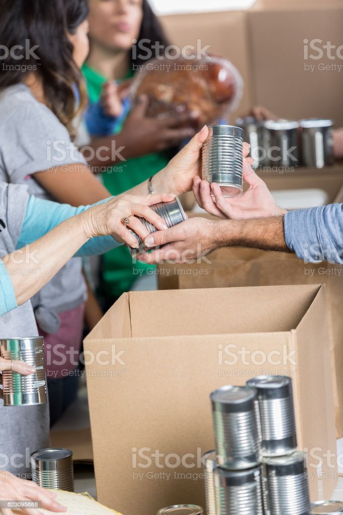 Man donates canned goods at food bank stock photo