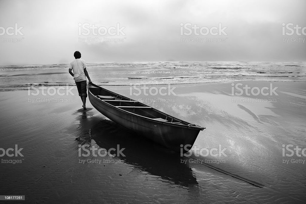 Man Dragging Canoe Boat into Ocean, Black and White stock photo
