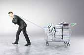 Man dragging trolley with books