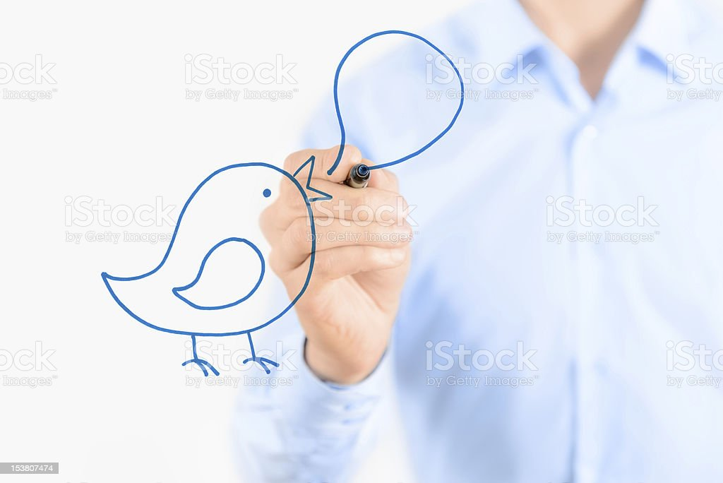 Man drawing a blue bird with a speech bubble royalty-free stock photo
