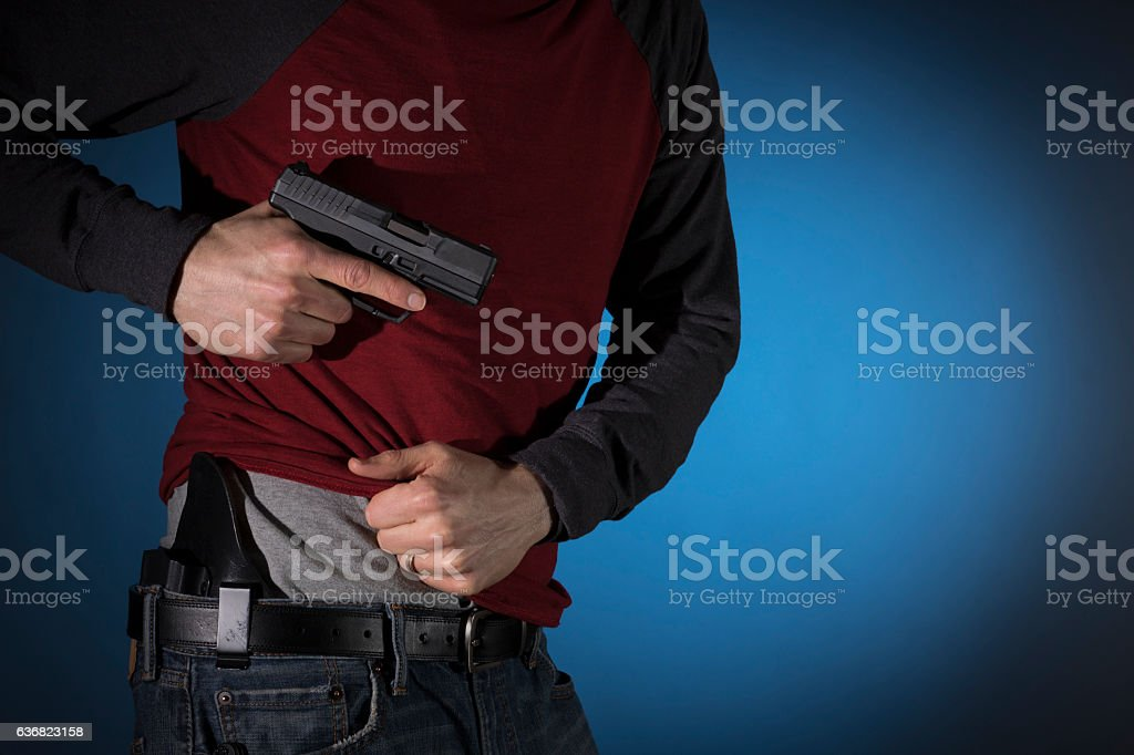Man drawing a concealed carry pistol from a holster stock photo