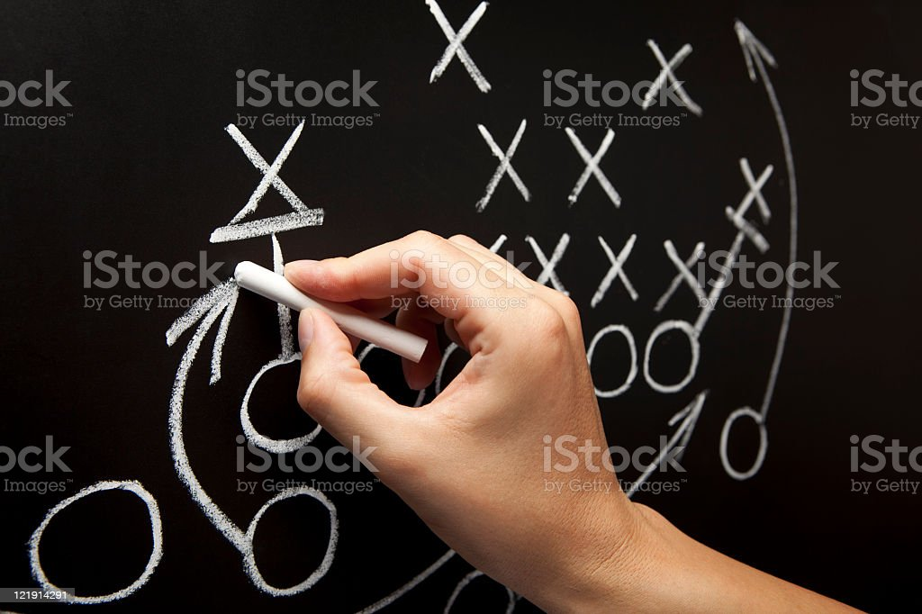 Man drawing a game strategy on a chalkboard stock photo