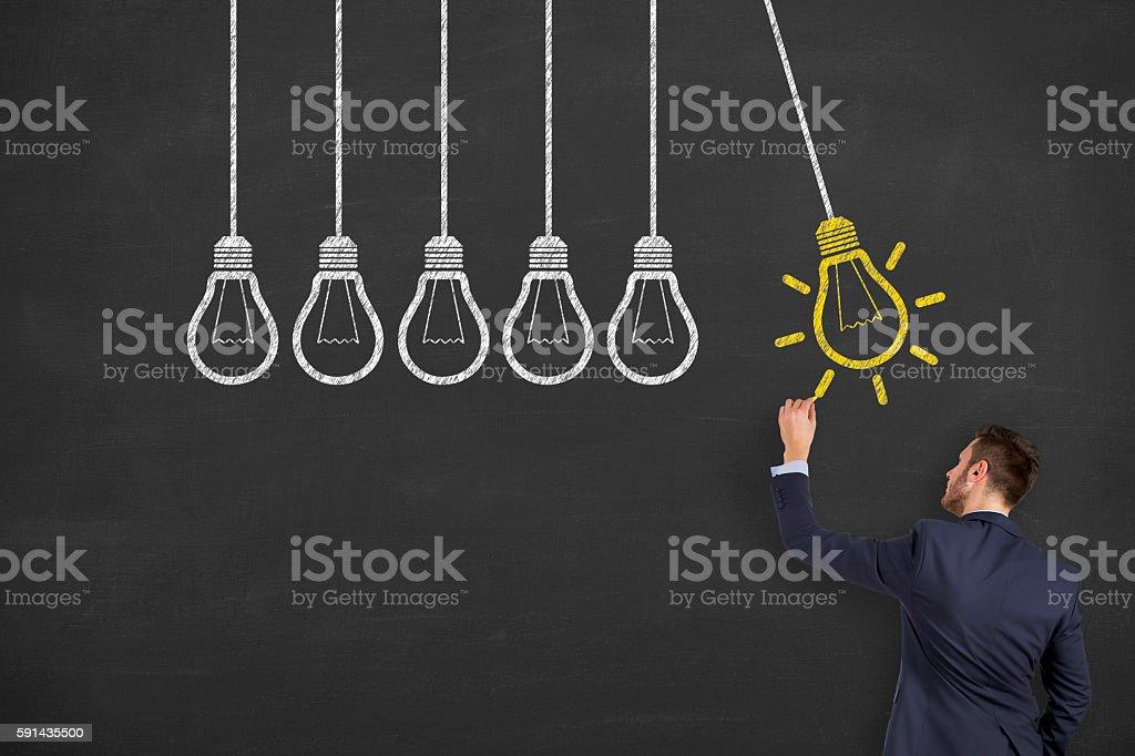 Man Drawing Light Bulb on Chalkboard stock photo