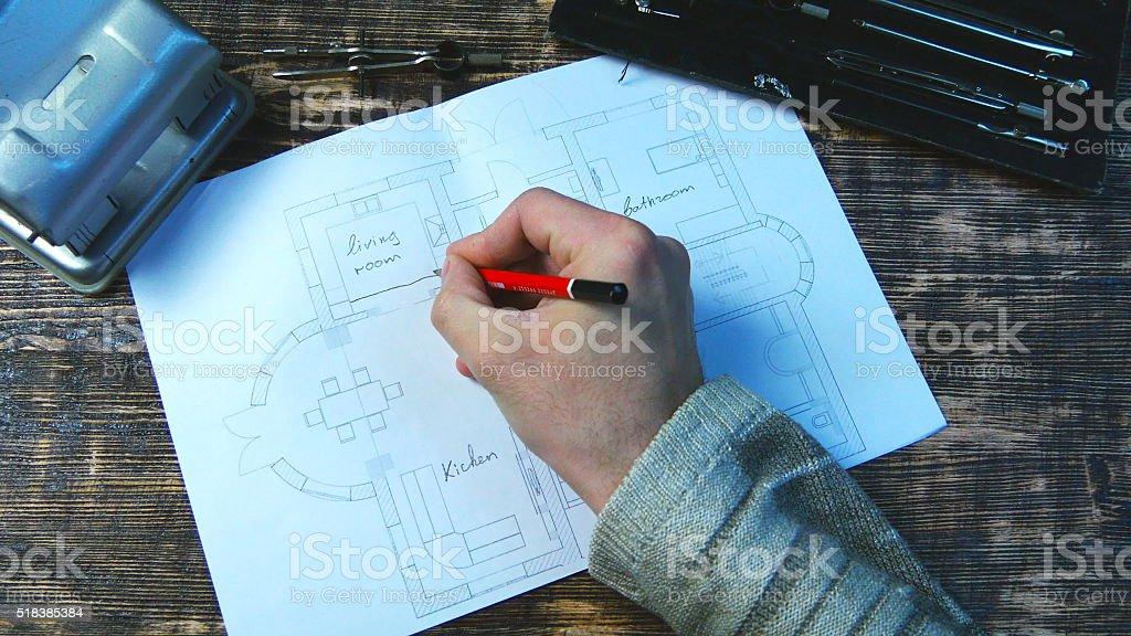 Hombre apoya un proyecto. Indica las dimensiones de las habitaciones foto de stock libre de derechos